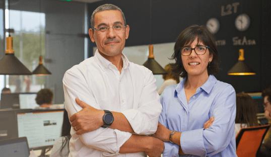 Fundadores da Last2Ticket a sorrir no escritório com tecnologia de eventos à sua volta