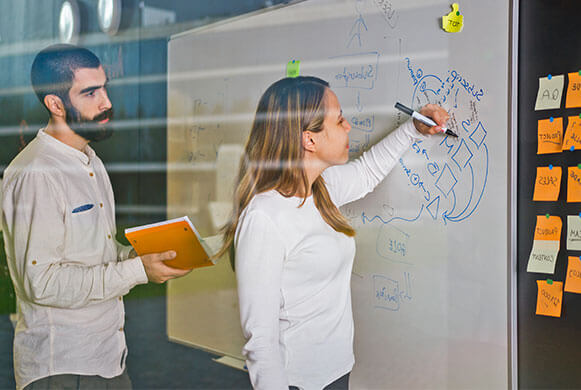 Dois colegas a escrever num quadro sobre planear um evento